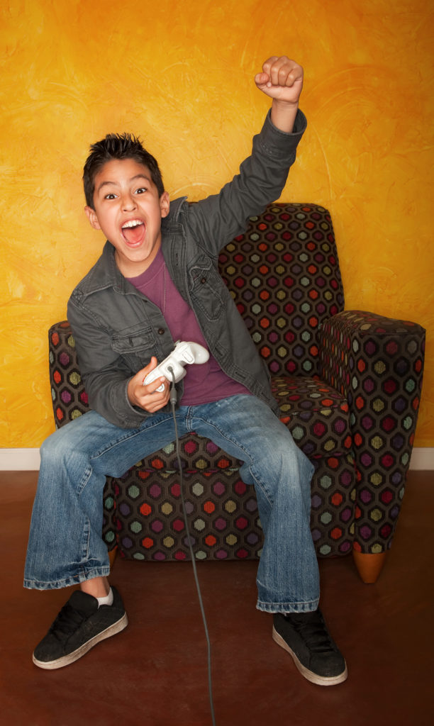 Handsome young Hispanic boy playing a video game